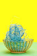 blue string in glass bowl object on yellow green background