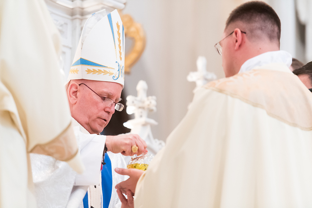 DENVER, CO - MAY 13: Denver Archbishop Samuel Aquila anoints the hands of Nicholas Larkin IV with Sacred Chrism during his ordination to the priesthood at the Cathedral Basilica of the Immaculate Conception on May 13, 2017, in Denver, Colorado. (Photo by Daniel Petty/for Denver Catholic)