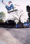 A skateboarder skateboarding in the air.