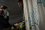Greece, Idomeni, <br /> <br /> Pediatrician Dr. Sophia Schuler, age 32, from Red Cross Hungary is given a medical checkup for  a Syrian boy, who suffered badly from high fever and severe colds.<br /> <br /> Red Cross Team from Hungry during their shift at the Emergency Room. Hospital which is a small tent. Difficult cases will be taken to the hospitals in Polycastro or Thessaloniki. March 2016<br /> <br /> keine Veroeffentlichung unter 50 Euro*** Bitte auf moegliche weitere Vermerke achten***Maximale Online-Nutzungsdauer: 12 Monate !!