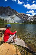 Hiker purifying water at Fern Lake, Ansel Adams Wilderness, June Lake, California USA