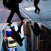 Pedestrians and buildings are reflected in a puddle in Times Square, New York, February 18,, 2010.