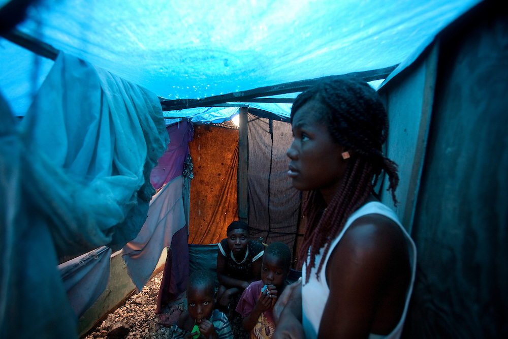 A woman in the makeshift refugee camp, La Piste, in Port-au-Prince, Haiti try to hide from the rain in her shack on July 15, 2010. La Piste (French for &quot;runway&quot;)is a settlement sprawled across the site of a disused airport and now home to an estimated 20,000 earthquake survivors living in makeshift structures.<br /> Six month after a catastrophic earthquake measuring 7.3 on the Richter scale hit Haiti on January 13, 2010, killing an estimated 230,000 people, injuring an estimated 300,000 and making homeless an estimated 1,000,000.