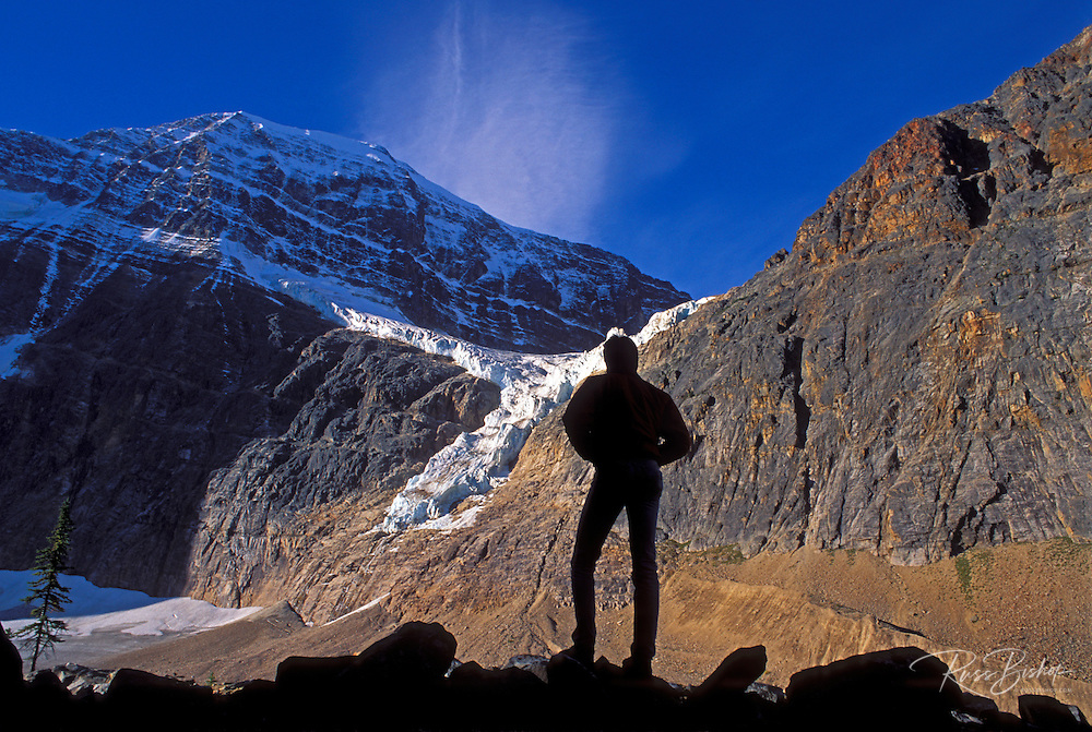 Hiker silhouetted against morning light on Mount Edith Cavell and the Angel Glacier in the Canadian Rockies, Jasper National Park, Alberta, Canada
