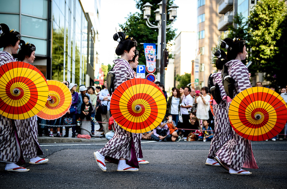 Women wearing traditional clothing and carrying umbrellas walk in a parade at the 2015 Nagoya Festival in Nagoya, Japan.