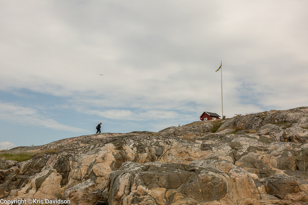 Man trudging up a cliff towards a small, red lighthouse on Vrångö (an island in the Gothenburg archipelago).