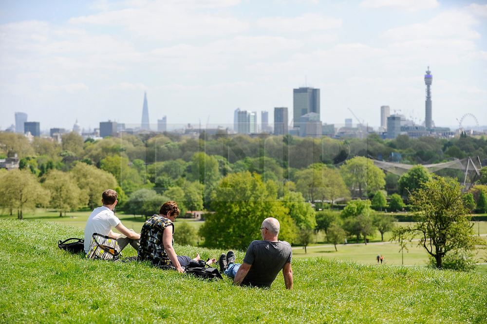© Licensed to London News Pictures. 04/05/2018. LONDON, UK.  A family enjoys the sunshine and warm temperatures in Primrose Hill.  Forecasters predict that the upcoming Bank Holiday Monday could see temperatures exceed 25C.  Photo credit: Stephen Chung/LNP