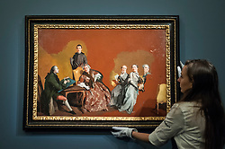 "© Licensed to London News Pictures. 06/07/2015. London, UK.  A Sotheby's technician shows ""The artist's family"" by Giovanni Domenico Tiepolo (est. £2.5m to £3.5m) at the preview of Old Masters, British Paintings and Masterworks from the collection of Castle Howard at Sotheby's ahead of the auction on July 8. Photo credit : Stephen Chung/LNP"