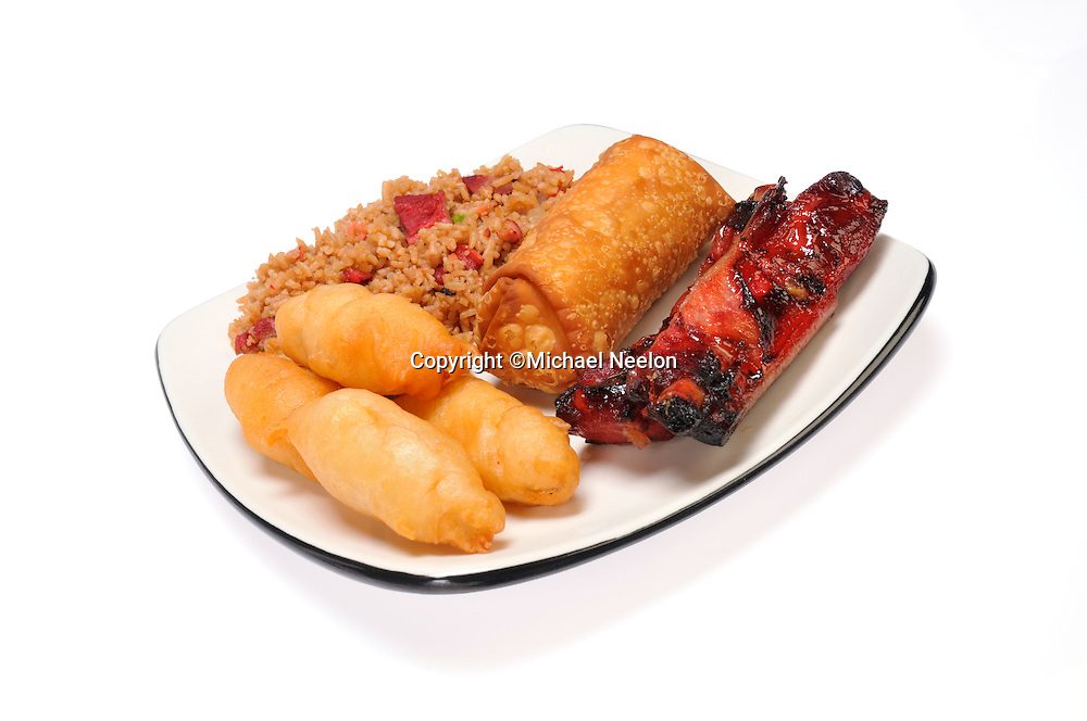 Chinese food dinner of pork fried rice chicken fingers spare ribs and egg roll on white plate on white background.
