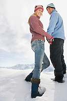 Couple standing on snow covered hill portrait low angle view