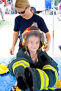Girl age 6 trying on firefighter jacket and helmet at rescue demonstration. Aquatennial Beach Bash Minneapolis Minnesota USA