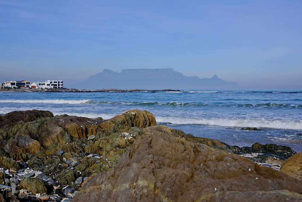 Table Mountain,Cape Town, South Africa. . A blanket of smog covers the base of Table Mountain in the early winter morning. Expensive properties flank the shoreline.