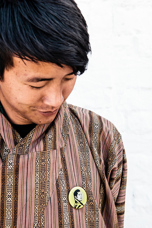 Staff at Bhutan Spirit Sanctuary with button of king of Bhutan