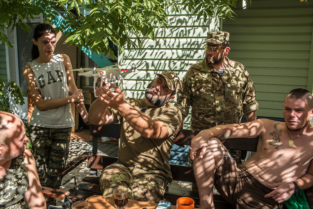 MELEKYNE, UKRAINE - AUGUST 30, 2015: Fighters from the Donbass Battalion, who gave only their war names (from left Khats, Kazbeg, Sobol, and Yakut), and Sveta, second from left, who is not a fighter, relax at the group's base in Melekyne, Ukraine. Kazbeg is holding a small drone, which they use during fights to conduct reconnaissance. Many of the formerly autonomous battalions have recently been pulled back from the front line and replaced by regular Ukrainian soldiers, which has frustrated some of the fighters, who consider themselves battle-tested and eager to continue the fight. CREDIT: Brendan Hoffman for The New York Times