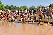 Young children jump into a muddy watering hole at the 2015 National Red Neck Championships May 2, 2015 in Augusta, Georgia. Hundreds of people joined in a day of country sport and activities.