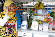 Nur Khayati, 24, talking on her mobile phone.<br /> <br /> Nur was working in a restaurant when she downloaded the Usaha Wanita app. She wasn't planning to go into business then but the stories and advice about the need for women to be independent inspired her so much that she decided to invest her savings in setting up a juice stall.<br /> <br /> Her fruit is purchased daily and the juices are freshly prepared in front of the customer. <br /> <br /> Her business is just four months old but is already thriving. She has been able to give her parents 6 million rupiah, which they are investing in land to increase the size of their fruit farm. <br /> <br /> She is also opening a new booth in another part of town in two weeks time.
