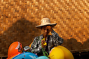 A young street vendor, offering inflatable toys, in one of the improvised narrow streets of Shwet Set Taw. Shwet Set Taw, Magwai Division, Myanmar. February 2014.