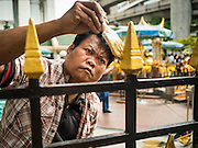 22 AUGUST 2015 - BANGKOK, THAILAND: A worker paints the iron fence around the Erawan Shrine in Bangkok. The fence was damaged by a terrorist's bomb earlier in the week. Erawan Shrine in Bangkok reopened Wednesday, August 19, after more than 20 people were killed and more than 100 injured in a bombing at the shrine Monday, August 17, 2015. The shrine is a popular tourist attraction in the center of Bangkok's high end shopping district and is an important religious site for Thais. No one has claimed responsibility for the bombing.             PHOTO BY JACK KURTZ