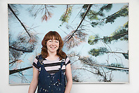 Mid adult woman standing in front of large painting