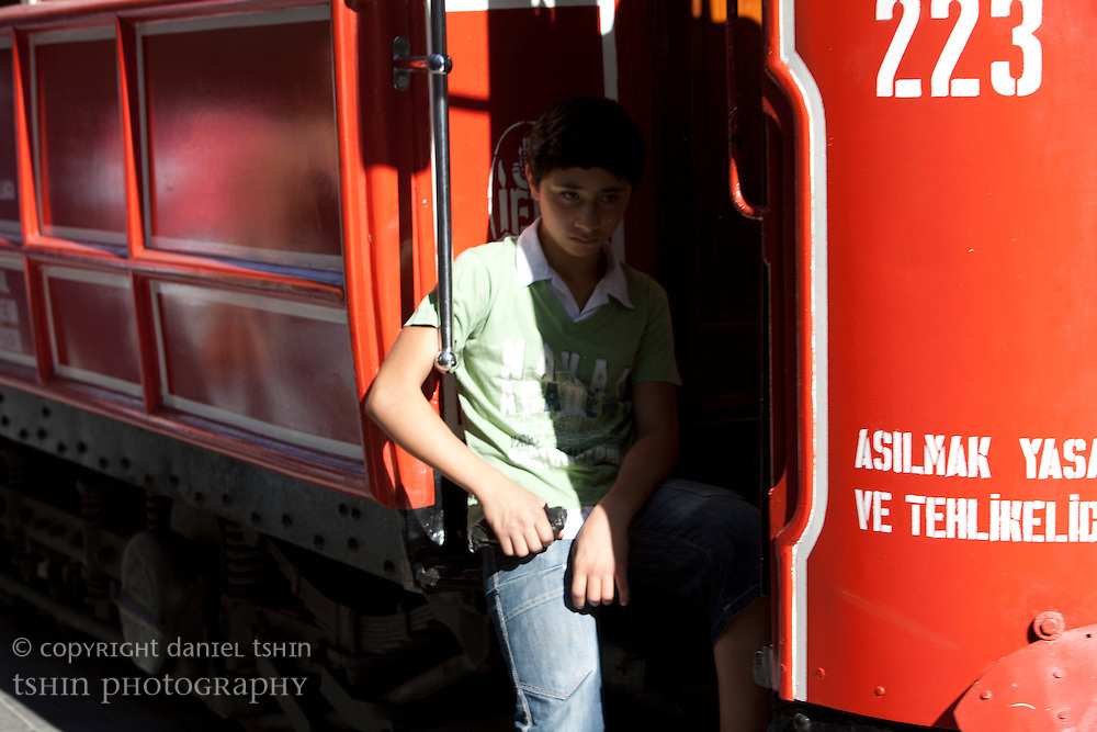 Local boy hanging off the historic tram full of passengers as it travels along ?stiklal Avenue in Beyo?lu, a walking street which is full of pedestrians.