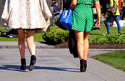 Two women wearing short skirts walk in the sunshine as upskirting, the invasive practice of taking an image or video up somebody???s clothing, becomes a specific criminal offence in England and Wales, punishable by up to two years in custody.