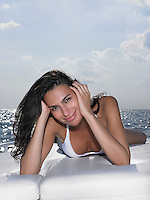 Young woman in bikini lying on cushions on yacht