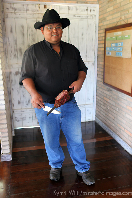 """South America, Brazil, Pantanal. A Pantaneiro serving a barbeque lunch """"cowboy style"""" at the Cordilheira Lodge of the Caiman Ecological Reserve."""