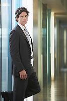 Businessman standing in office corridor portrait