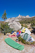 Woman relaxing in camp under Echo Peaks (climbing gear visible), Yosemite National Park, California