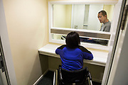 A prisoner on a closed visit sits talking to his wife. Closed visits take place in locked rooms with a toughened glass window between the prisoner and his visitor.  HMP/YOI Portland, Dorset. A resettlement prison with a capacity for 530 prisoners. Portland, Dorset, United Kingdom.