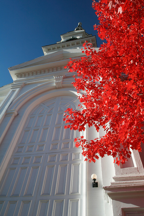 Brilliant red maple against a blue sky and the Unitarian Church in Montpelier, VT.