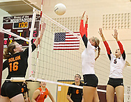 Solon's Jordan Runge (16) tries to tip the ball over the hands of Maquoketa's Erica Sutton (7) and Allison Vandemore (5) during the WaMaC Tournament Championship game at Mount Vernon High School in Mount Vernon on Thursday October 11, 2012. Solon defeated Maquoketa 17-25, 25-15, 15-10.