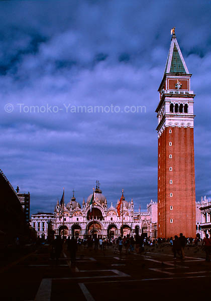 The Bell Tower of San Marco against heavy clouds but with several openings, lighting the Campanile of San Marco and the main facade of the Basilica at the Piazza, in Venice, Italy.<br /> Travel Photo of Venice, Italy by Tomoko Yamamoto. Original on 35mm film taken with an Olympus 24mm f/3.5 shift (PC) lens.