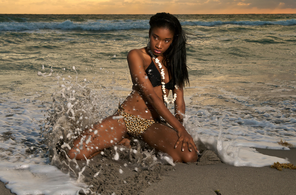 Young african american girl looks sensual in the beach.