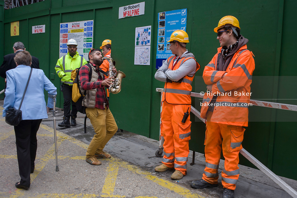 A saxophonist plays to bemused construction workers during a lunchtime break in the City of London.