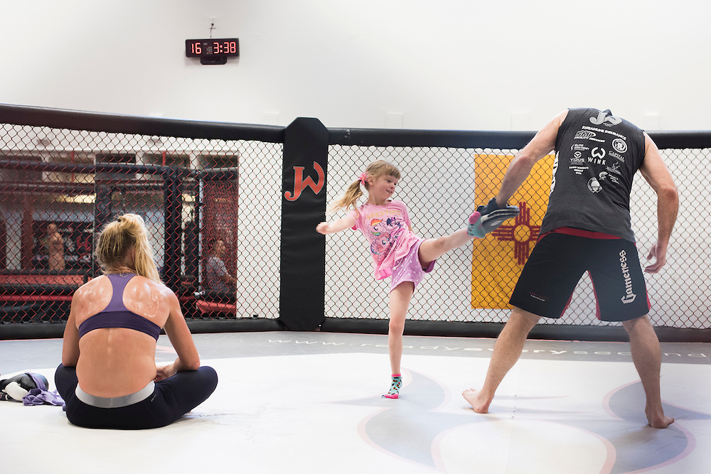 Coach Mike Winkeljohn plays with his daughter while UFC bantamweight Holly Holm looks on after a training session at Jackson Wink MMA in Albuquerque, New Mexico on June 10, 2016.