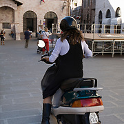 Woman riding motorscooter across Piazza del Comunale, Assisi, Italy PG<br />