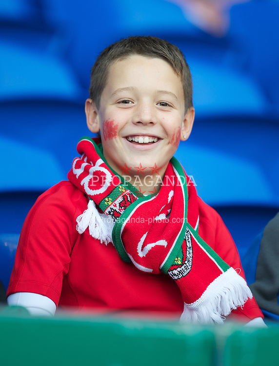 CARDIFF, WALES - Saturday, November 12, 2011: A Wales supporter with a free scarf before the international friendly match against Norway at the Cardiff City Stadium. (Pic by David Rawcliffe/Propaganda)