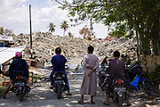 Villagers watch the road leading to the remains of Petobo, a village that was swallowed by a sinkhole or Liquefaction triggered by an earthquake of 7.5 earthquake magnitude that hit off the coast of Donggala, Palu Sulawesi Central, Indonesia on Sept. 28th.  About 1,700 houses were buried by mud.