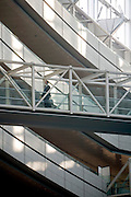 one businessperson walking over a bridge inside a modern office building