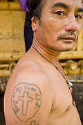 18 FEBRUARY 2008 -- BONG TI, KANCHANABURI, THAILAND: A cross tattooed on the arm of a Karen Christian refugee in a village near the Bamboo School in Bong Ti, Thailand, about 40 miles from the provincial capital of Kanchanaburi. Sixty three children, most members of the Karen hilltribe, a persecuted ethnic minority in Burma, live at the school under the care of Catherine Riley-Bryan, whom the locals call MomoCat (Momo is the Karen hilltribe word for mother). She provides housing, food and medical care for the kids and helps them get enrolled in nearby Thai public schools. Her compound is about a half mile from the Thai-Burma border. She also helps nearby Karen refugee villages by digging water wells for them and providing medical care. Thai authorities have allowed the refugees to set up the village very close to the border but the villagers are not allowed to own land in Thailand and they can't legally leave the area to get jobs in Thailand.    Photo by Jack Kurtz