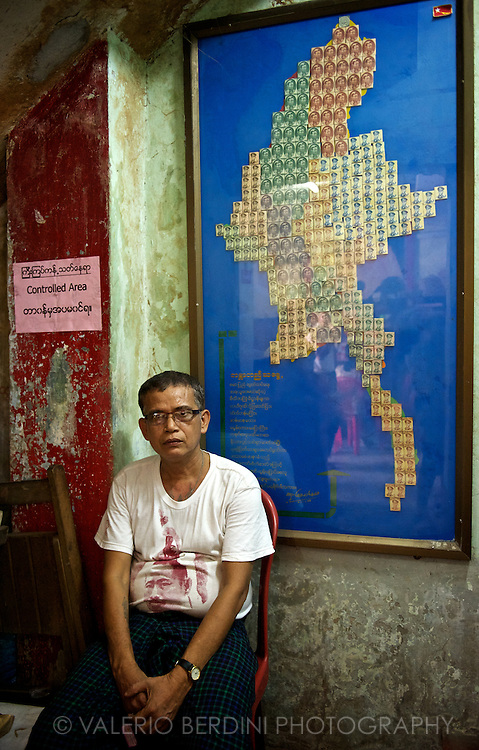 One of the staff of the NLD headquarter resting after the electoral rush in front of a collage map of Burma made with Aung San images taken from old banknotes..Yangon, Myanar. 2012
