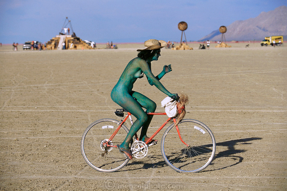 Green bicyclist rides by as they load the Burning Man, which has been lowered from its base, with explosives in preparation for the grand finale of burning it. Burning Man is a performance art festival known for art, drugs and sex. It takes place annually in the Black Rock Desert near Gerlach, Nevada, USA. Art installation.