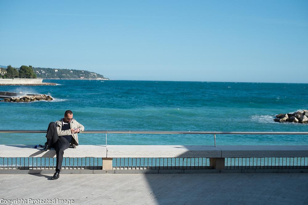 A man checks his cell phone while sitting by the Nouveau Musée National de Monaco.