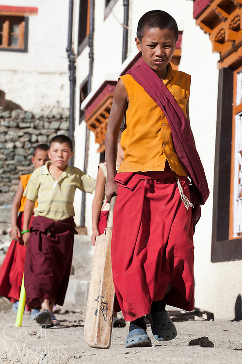Young Ladakhi Buddhist monks going to play cricket near Lamayuru Monastery, Ladakh, Northern India
