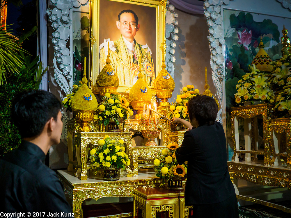 25 OCTOBER 2017 - BANGKOK, THAILAND: A woman lights a candle at a portrait of the late king during the funeral for Bhumibol Adulyadej, the Late King of Thailand. He died in October 2016 and was cremated during an ornate five day funeral on 26 October 2017. He reigned for 70 years and was Thailand's longest serving monarch.         PHOTO BY JACK KURTZ
