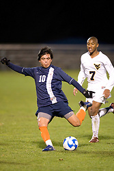 Virginia midfielder Jonathan Villanueva (10) shoots past West Virginia midfielder Gift Maworere (7).  The West Virginia Mountaineers defeated the Virginia Cavaliers 1-0 in the second round of the 2007 NCAA Men's Soccer Tournament at Dick Dlesk Stadium in Morgantown, WV on November 28, 2007.