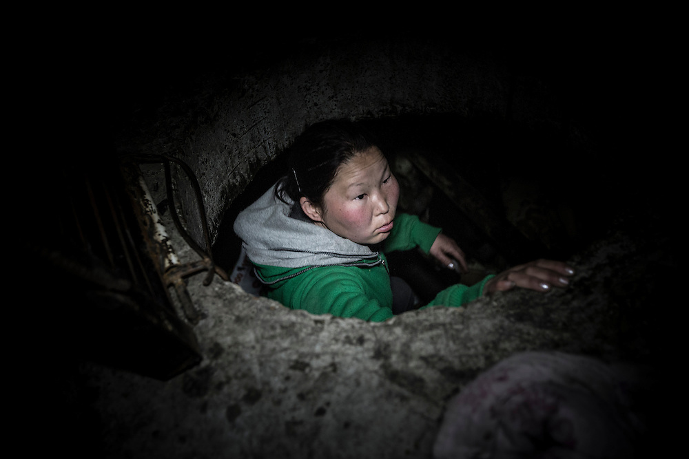 Young woman climbing out of a sewer, which she made home, in the streets of Ulan Bator