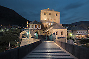 Stari Most or Old Bridge at night, a 16th century Ottoman bridge across the Neretva river, in Mostar, Bosnia and Herzegovina. The bridge was destroyed in the 1990s Yugoslavian war and has been rebuilt. The town is named after the mostari or bridge keepers of the Old Bridge. Mostar developed in the 15th and 16th centuries as an Ottoman frontier town and is listed as a UNESCO World Heritage Site. Picture by Manuel Cohen