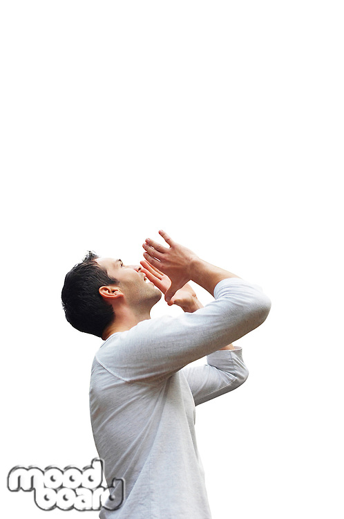 Profile shot of mid-adult man in casuals shouting over white background